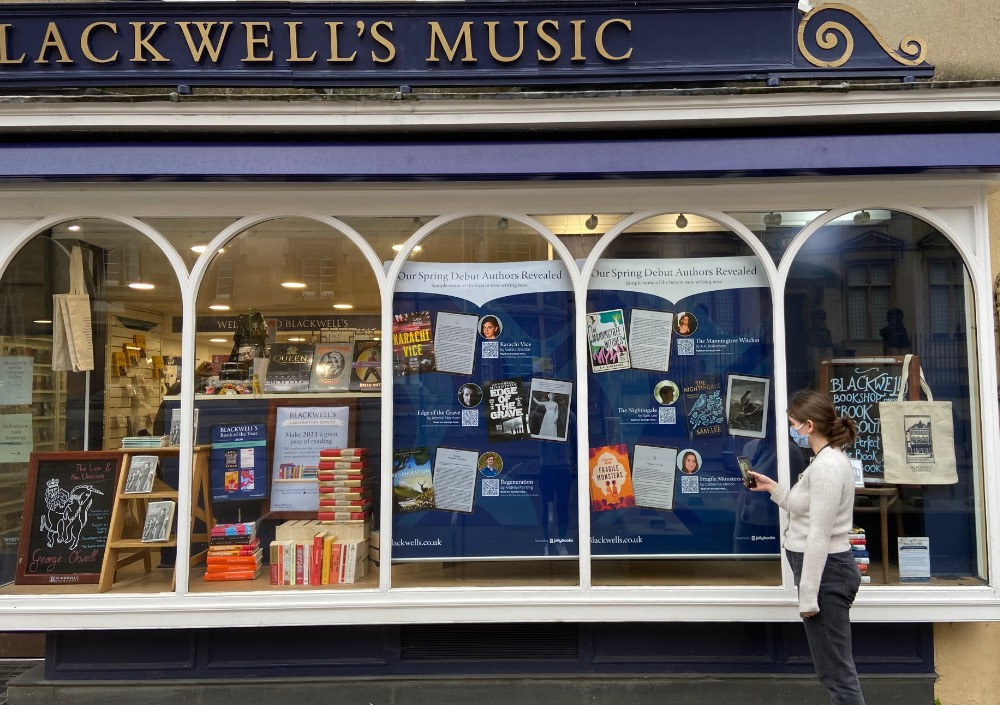 Photo of Blackwell's shop window showing large poster of new releases containing QR codes to open samples of books.